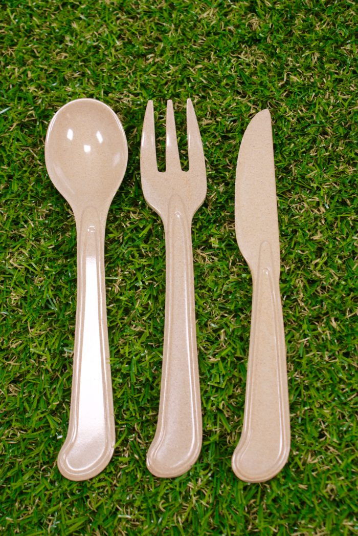 From left to right: brown rice husk spoon, fork and then knife. All laid on a green grass. Eco-friendly plastic-free cutlery alternatives.