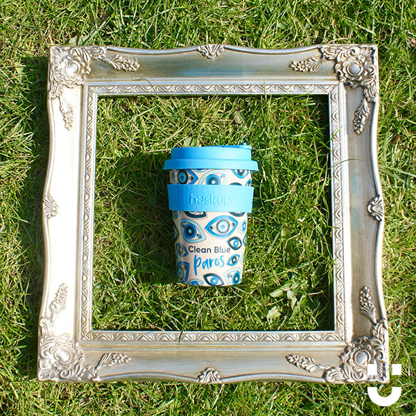 huskup reusable coffee cup with the Clean Blue Paros for Common Seas with a photo frame placed around it in a field of grass