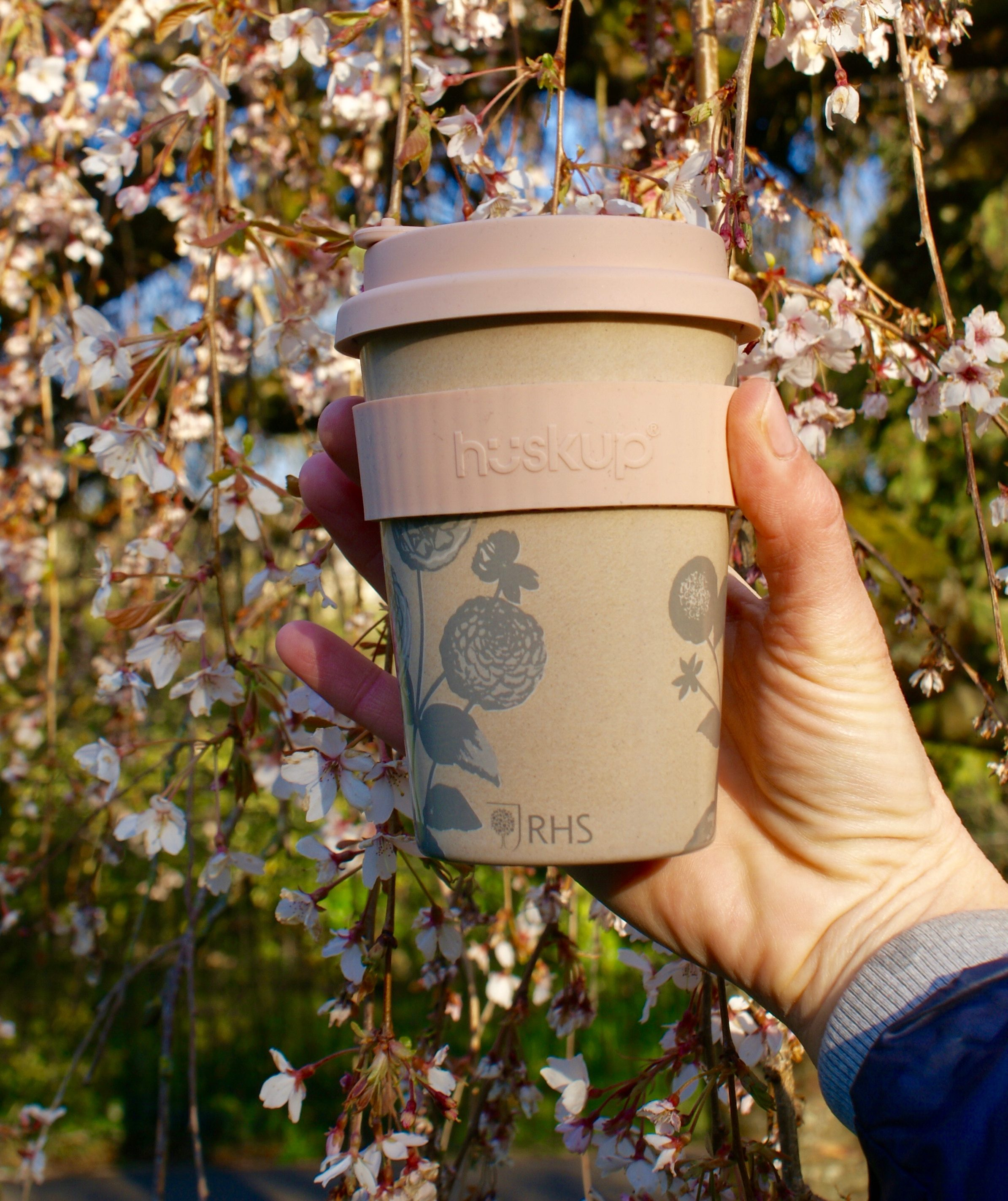 eco friendly reusable coffee mugs that can be customised with a pink band stood in front of a tree that has beautiful pink blossoms