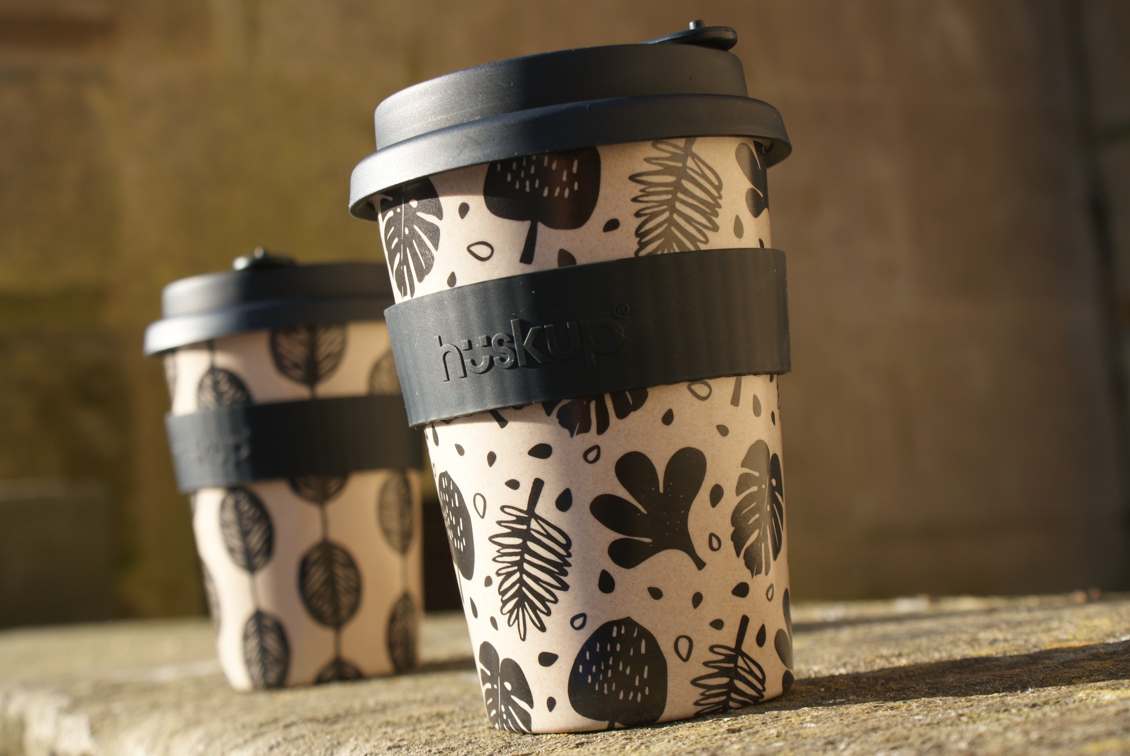 Two reusable cup huskups in the sun with black bands the one to the left has a black and brown leaf design and the one to the right has leaves and dots in different shapes and sizes the one on the right is placed closer to the camera