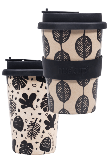 the black designs with leaves on two different cups placed right next to each other. The one on the left has the leaves falling randomly and the one on the right has the leaves stacked ontop of eachother