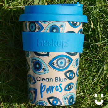 """Paros design huskup reusable coffee cup with blue heat resistant band that reads """"huskup"""" and blue lid"""