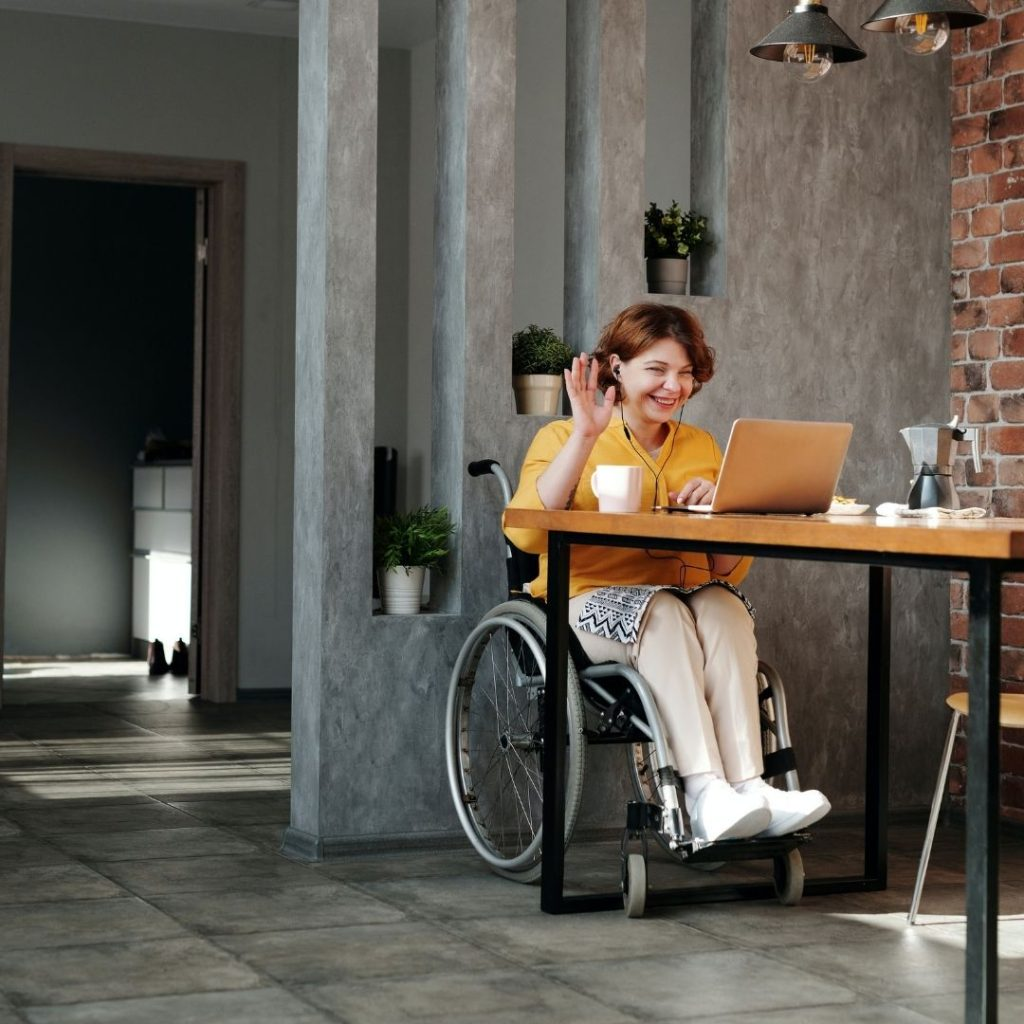 A women in a wheelchair sat in a meeting drinking some coffee